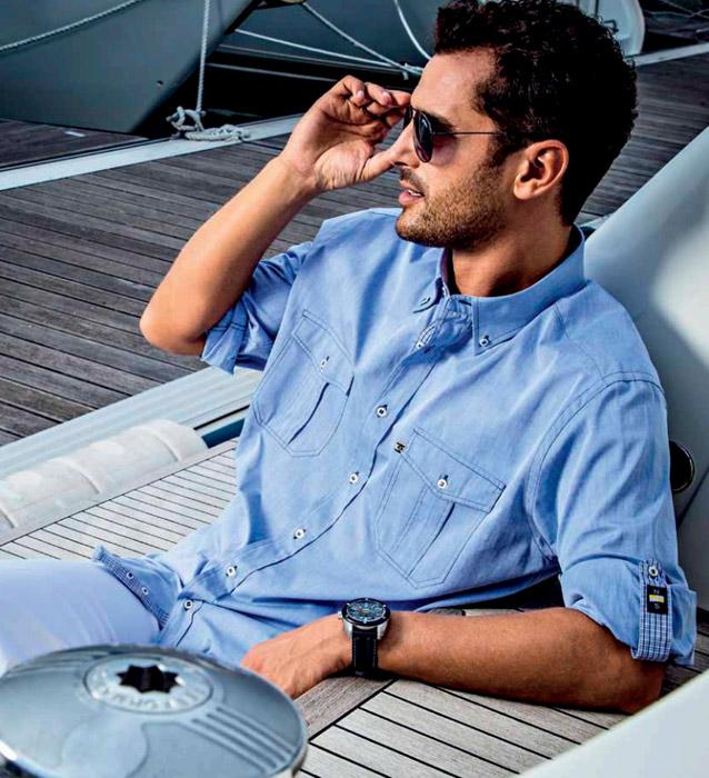 uomo-con-occhiali-da-sole-indossa-camicia-azzurra-con-due-taschini