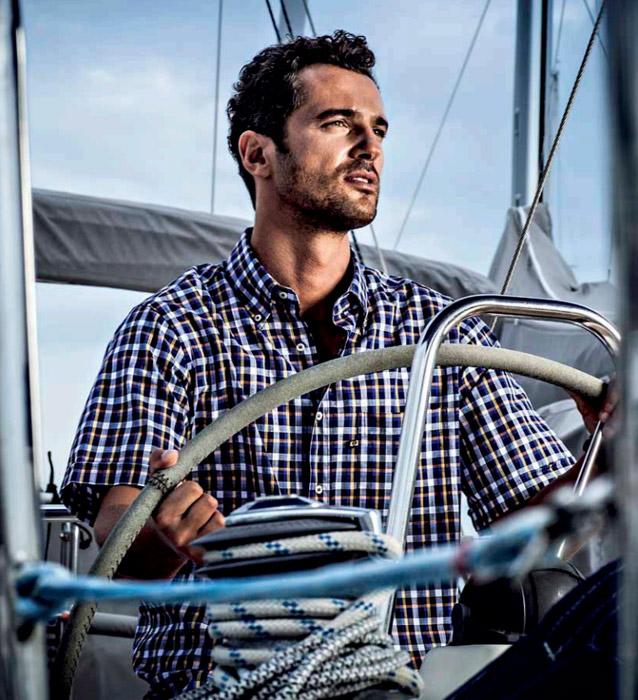 uomo-sulla-barca-camicia-quadri-blu